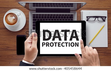 DATA PROTECTION, on the tablet pc screen held by businessman hands - online, top view - stock photo