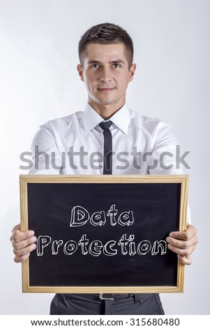 Data Protection - Young businessman holding chalkboard with text - stock photo