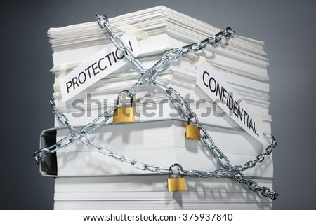 Data security. Protected documents. Confidential information. Locked pile of documents and folder. Gray background.  - stock photo