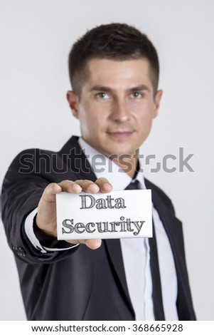 Data Security - Young businessman holding a white card with text - vertical image - stock photo