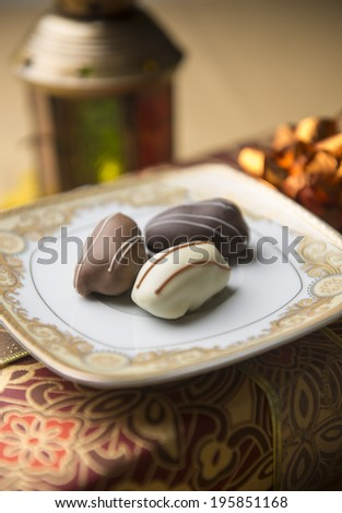 Date chocolates and a traditional lamp close up - stock photo