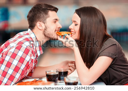 Date in bowling. Closeup image of young attractive woman and man eating one piece of pizza with bowling alley in the background  - stock photo