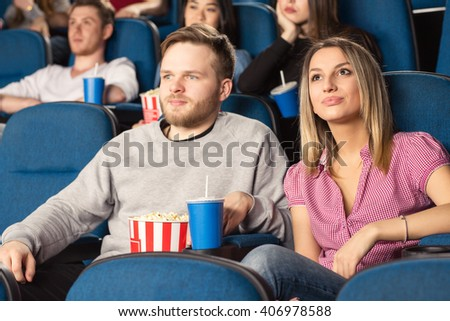 Date night. Shot of a young cheerful couple at the cinema