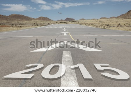 Date numbers 2015 hovering on airport runway with direction markings and mountains in the background - stock photo