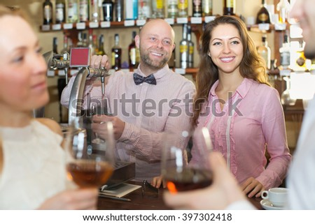 Date of cheerful couple drinking wine at bar and smiling. Focus on girl - stock photo