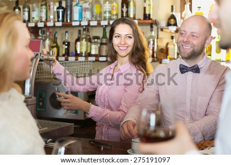 Date of young cheerful couple drinking wine at bar and smiling. Focus on girl