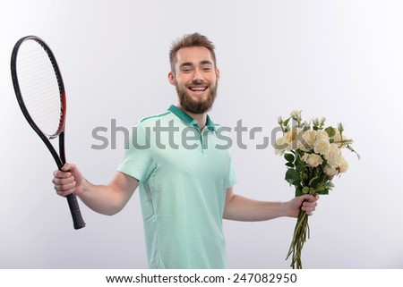 Date on the tennis court. Handsome young man holding tennis racket in one hand and flowers in the other while standing isolated on white background - stock photo