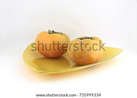 date plums on a plate on light background