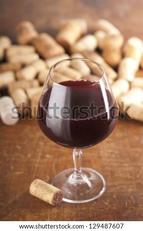 Dated wine bottle corks and red wine on the wooden background. Close up