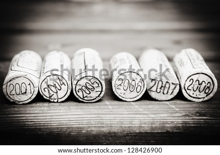 Dated wine bottle corks on the wooden background. Black and white - stock photo