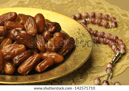 dates and Islamic rosary - stock photo