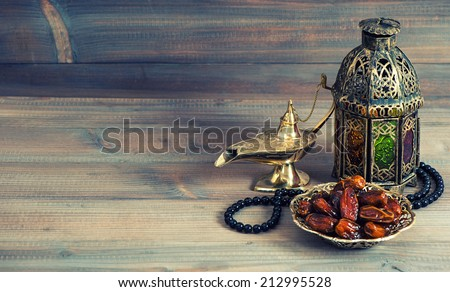 Dates, arabian lantern and rosary. Islamic holidays concept. Ramadan decoration. Retro style toned picture - stock photo