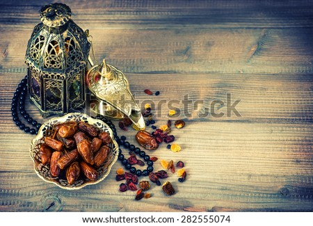 Dates, arabic lamps and rosary. Islamic holidays decoration concept. Vintage style toned picture - stock photo