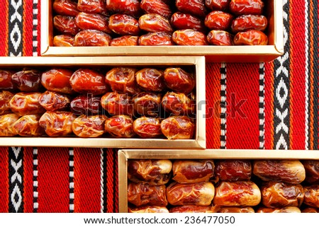 Dates arranged on Arabian woven fabric. Dates symbolise Arabian hospitality  - stock photo