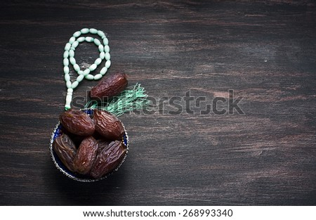 Dates fruit and rosary still life, on a dark wooden background - stock photo
