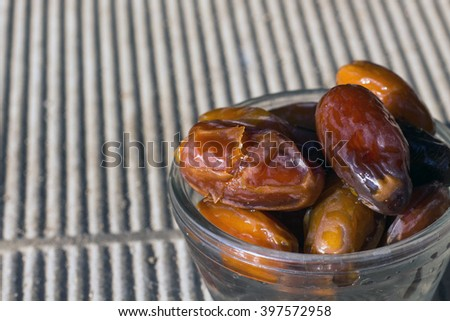 Dates fruit in a bowl closeup on wooden sunlight background. Dates fruit. Date fruit on wooden table. - stock photo