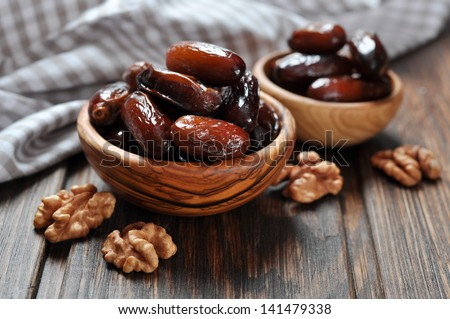 Dates fruit in a wooden bowl closeup on wooden background - stock photo
