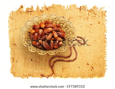 dates in a bowl and islamic rosary image on papyrus paper texture - stock photo