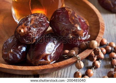 Dates on wooden plate with glass of tea and wooden rosary. Selective focus. - stock photo