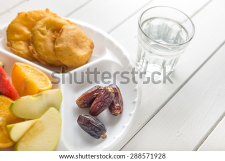 Dates with fruits and fried snacks. Food to break fast during holy month of Ramadan. - stock photo