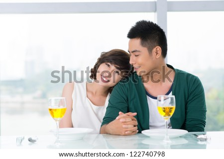 Dating couple holding hands in a cafe - stock photo