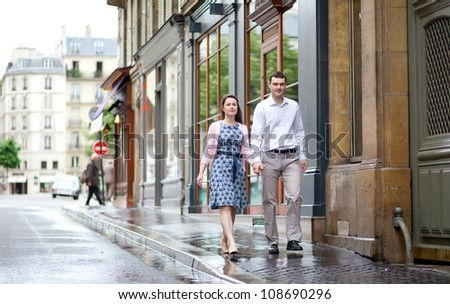 Dating couple walking in Paris after the rain