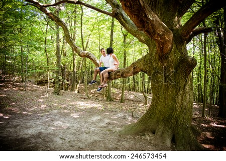 Dating in nature - young couple sitting together on big tree