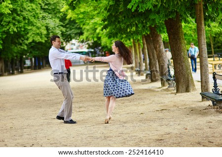 Dating romantic couple dancing in the Luxembourg garden of Paris - stock photo
