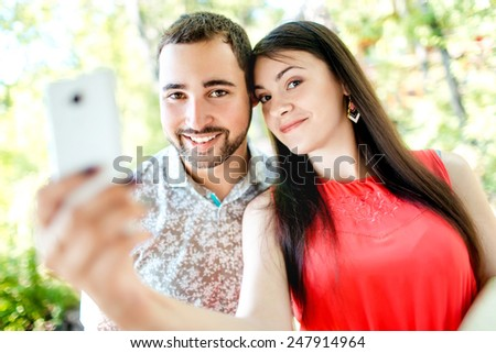 Dating young couple happy in love taking selfie self-portrait photo outdoors in a park, bright sunny day in summer. Beautiful young tourists having fun date. Caucasian man and woman. Shallow DOF. - stock photo