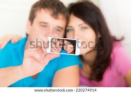 Dating young couple in love taking selfie at home - stock photo