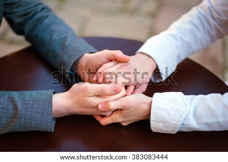 dating, young fashion elegant stylish couple sitting at a table in a cafe , gently hold hands, on streets of old european city - stock photo