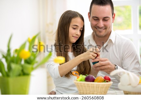Daughter and father having fun with Easter eggs, breaking colorful eggs - stock photo
