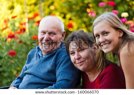Daughter and granddaughter visiting their kind grandfather. - stock photo