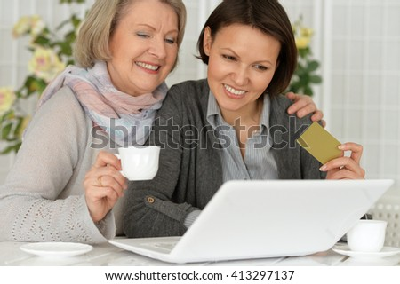 daughter and mother are shopping on the Internet with a credit card
