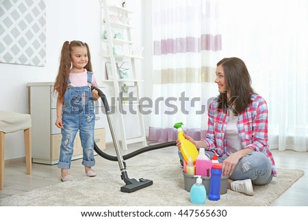 Daughter and mother cleaning house together - stock photo