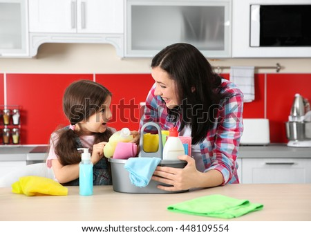 Daughter and mother in kitchen with cleaning set - stock photo