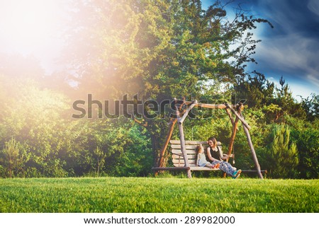 daughter and mother on the wooden swing on the horizon sunset green grass - stock photo