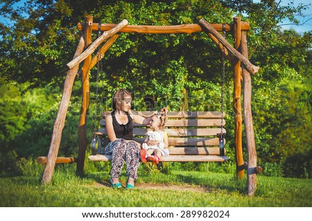 daughter and mother on the wooden swing on the horizon sunset green grass