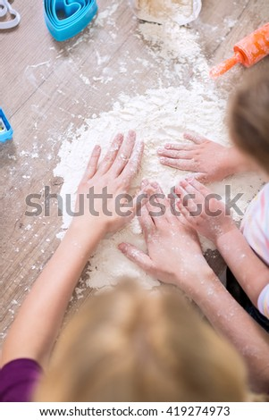 Daughter and mother playing with white flour close up
