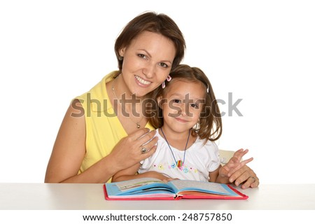 Daughter and mother read the book at home - stock photo