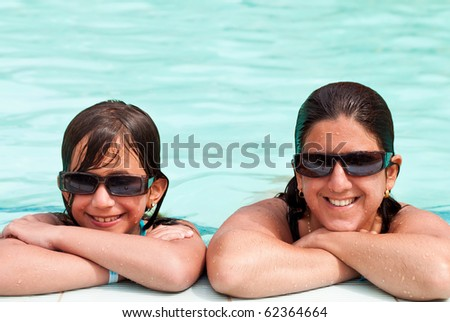 Daughter and mother smiling and wearing sunglasses at the border of a swimming pool