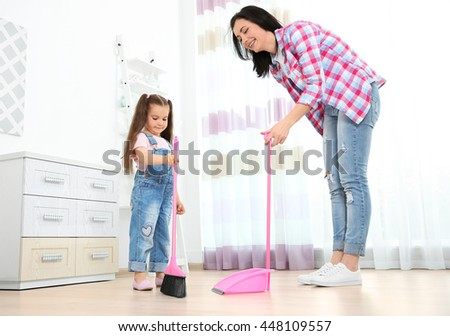 Daughter and mother sweeping together in room