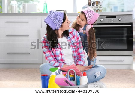 Daughter and mother with cleaning set in kitchen - stock photo
