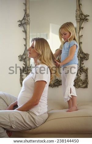 Daughter Braiding Pregnant Mother's Hair - stock photo