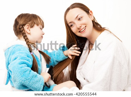daughter brushing her mother's hair in bed at home - stock photo