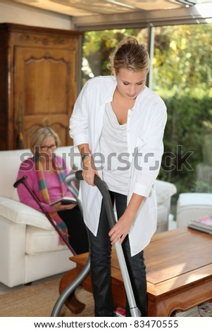 Daughter cleaning for mother - stock photo