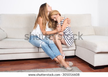 Daughter comforting her mother - stock photo