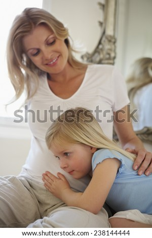 Daughter Cuddling with Pregnant Mother - stock photo