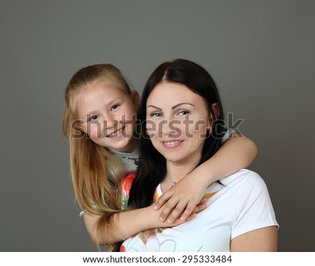 Daughter embraces her mother on gray background - motherhood, family relationships,