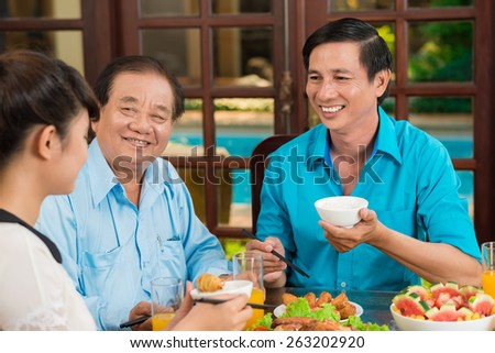 Daughter, father and grandfather dining together - stock photo